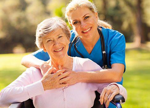 Pflegerin mit alter Dame im Rollstuhl