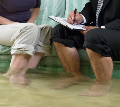 Frau und Mann auf Couch bei Hochwasser