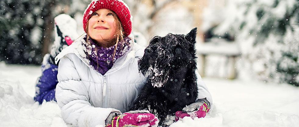 Mädchen sitzt mit ihrem Hund im Schnee