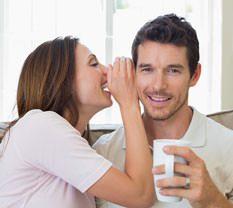 Frau flüstert Mann etwas ins Ohr