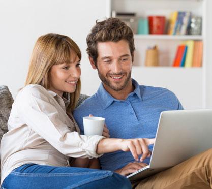 Pärchen sind mit dem laptop auf der Couch