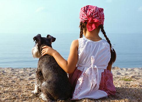 Mädchen mit dem Hund am Strand