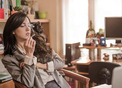 Frau raucht mit Katze auf der Schulter