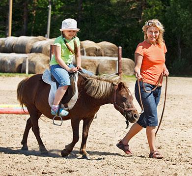Kleines Mädchen beim Ponyreiten