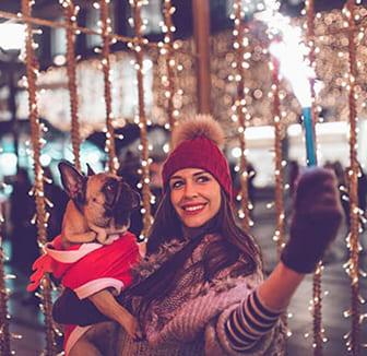 Frau feiert Silvester mit Ihrem Hund auf dem Arm