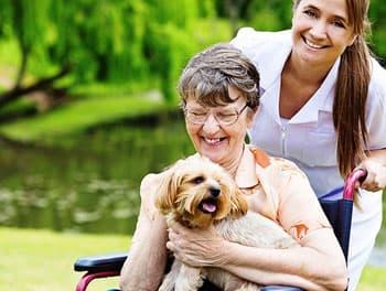 Alte Dame streichelt lachend ihren Hund