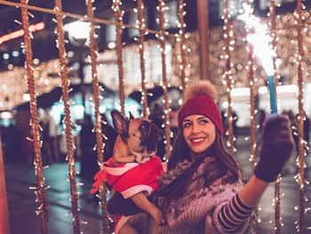 Junge Frau feiert Silvester und hält ihren Hund im Arm