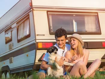 Paar mit dem Hund vor dem Wohnwagen