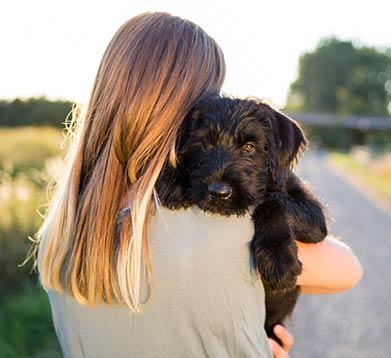 Frau mit ihrem Hund auf dem Arm