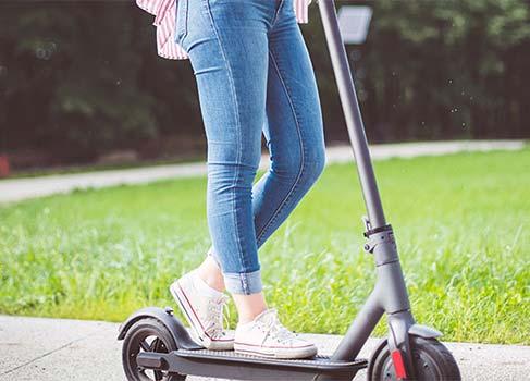 Junge Frau auf dem E-Scooter