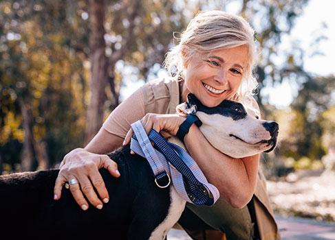 Frau umarmt ihren Hund