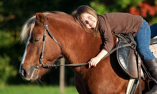 Mädchen reitet auf dem Pony