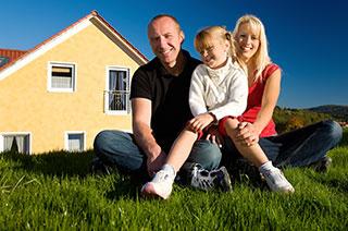 Glückliche Hausbesitzer vor dem Eigenheim
